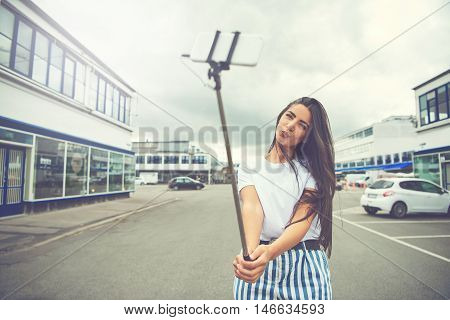 Cute woman with long hair and blue striped pants in charming pose taking a self portrait using a smart phone attached to a long pole known as selfie stick in the middle of street