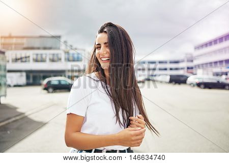 Cute young woman laughing and holding her hands while standing outside in large parking lot