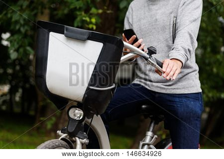 Man in casual clothing sitting on his bike with mobile phone