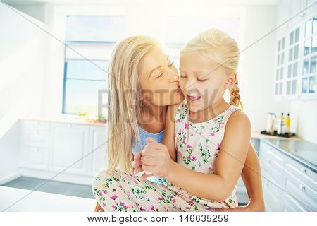 Beautiful young blond mother kissing daughter in ponytails and dress while she plays with bread dough