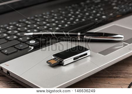 USB Flash drive lying on computer laptop keyboard and pen as background