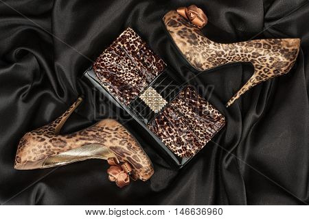 Leopard lacquer bag and leopard shoes on a black crumpled fabric