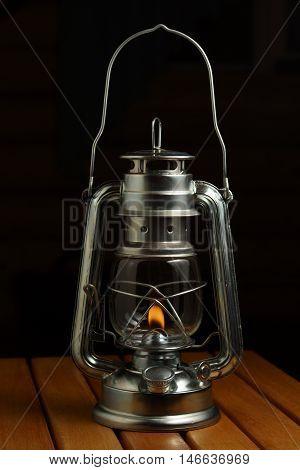 Kerosene lamp on the wood. Black background
