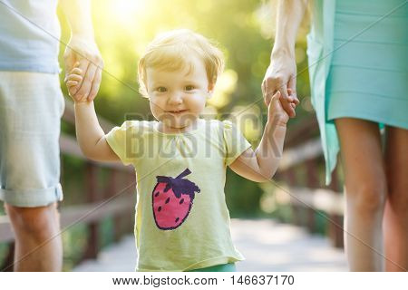 Parents holding little girl for hands in summer park.Image with lens flare effect