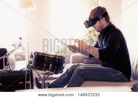 Young Adult Playing Drums At Home Using Viewer For Virtual Reality