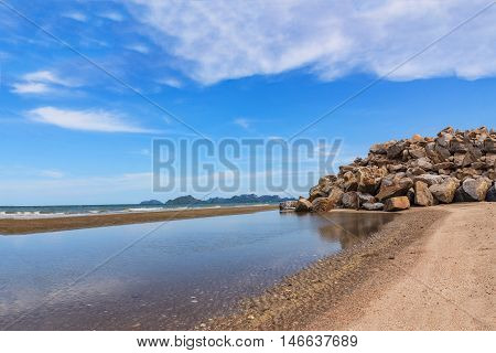 Landscape on the beach with a rock breakwater in Thailand