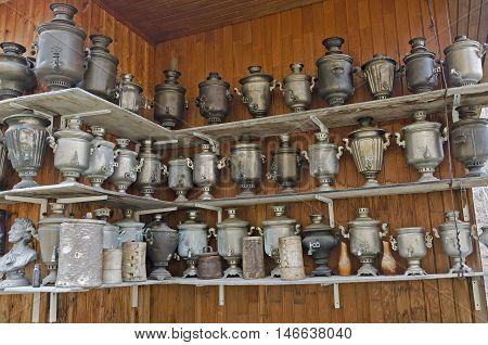 A large number of antique samovars on the shelves