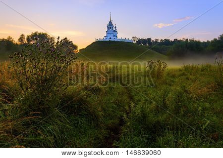 Russian christian church on hill foggy morning swamp landscape