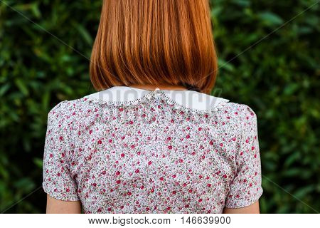 Back of redheaded woman in dress with white lace collar closeup