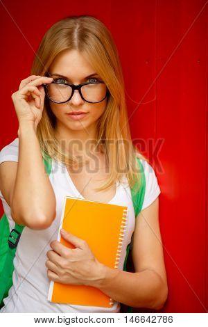 Blonde adjusts glasses on empty Burgundy background