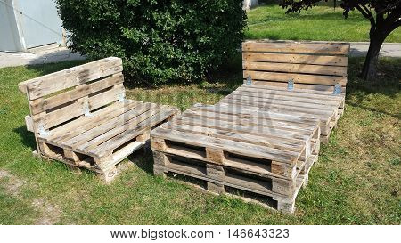 Table and sofa with wooden pallets on the grass