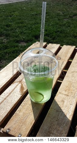 Mohito, mojito in a plastic cup with a straw on a wooden table