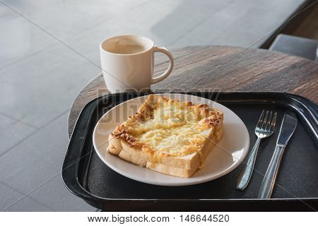 hot fresh coffee in white cup with silver spoon on wooden brown table and sandwich ham cheese plate silver fork and spoon at coffee time