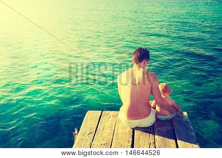 Young Father with His Little Baby Sitting on the Pier and Relaxing by the Sea. Rear View. Ripple Water Background. Dad and Son Concept. Warm Toned and Filtered Photo.