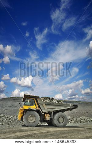 Heavy mining truck loaded with iron ore on the opencast side view