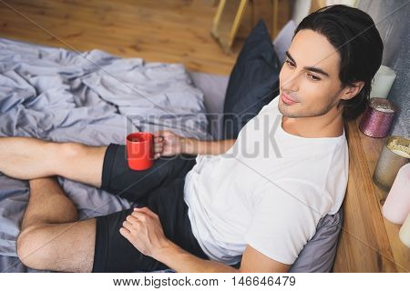 lonely man looking to nowhere while holding mug of coffee