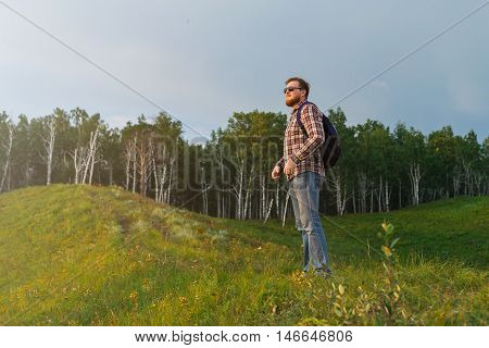 A man stands on a hill and watching the sunset. A tourist with a backpack walking through the hills and forests green grass. Evening sunset light. A guy with a beard in a plaid shirt meets the sunset in nature. A lone traveler.