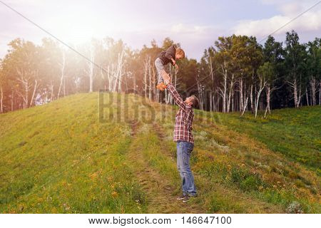 Father tossing up his son. The concept of oneness with nature family relationships and values. Camping. Playing with your child. Flight and fun. Confidence.