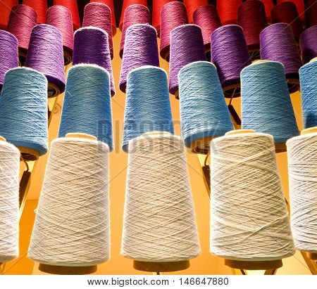 Spools of colorful thread used for weaving, stitching and designing in the fashion and textile industry.
