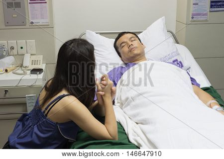 man a husband on bed as patient in hospital or clinic with woman a wife take care on hospital bed side with love and care
