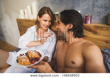 close up of a girl feeding her boyfriend in a bed
