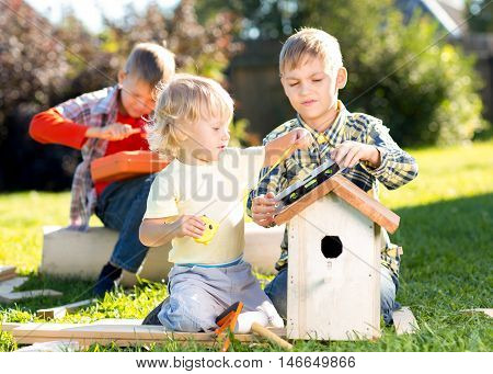 Three little boys brothers building birdhouse outdoors