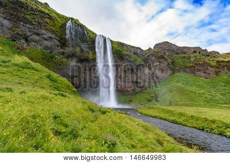 view of beautiful waterfall Seljalandsfoss in summer south Iceland; selective focus