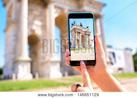Holding phone with photo of triumphal arch in Milan city.