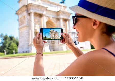 Young female tourist photographing triumphal arch in Milan city.
