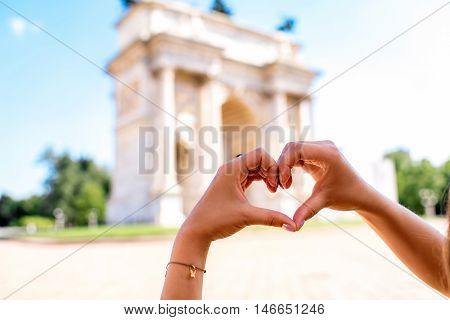Hands in form of the heart on the triumphal arch backround in Milan