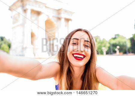 Young woman making selfie in front of the triumphal arch in Milan. Having great vacations in Milan