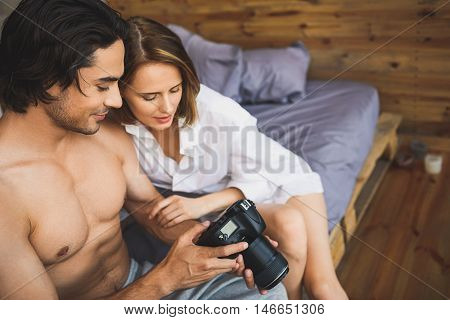 half-naked couple watching pictures on the digital photo camera while sitting on a bed