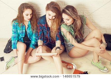 Three Students Girls Sitting on the Floor and Lokking at the Tablet. Street Style Trendy Teenagers. Casual Fashion Outfit. Youth Friendship and Lifestyle Concept. Top View. Toned Photo.