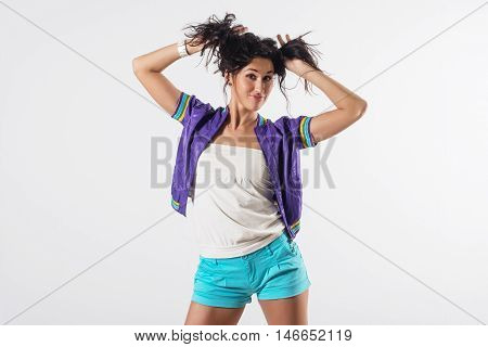 Young happy girl holding her hair, imitating tails hairstyle, wearing trendy outfit.
