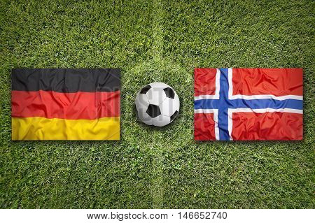 Germany vs. Norway flags on green soccer field 3D illustration