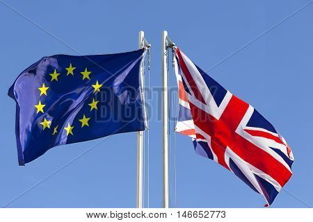 European Union flag and flag of UK on flagpole in front of blue sky