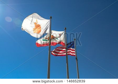 Cupertino, CA, USA - August 15, 2016: close up of flags in front of Apple Headquarters with American Flag and flag with Apple icon.