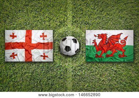 Georgia vs. Wales flags on green soccer field, 3D illustration