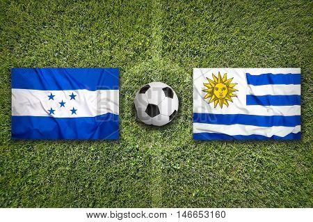 Honduras Vs. Uruguay Flags On Soccer Field, 3D Illustration