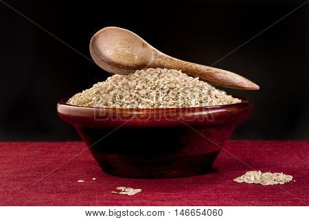 Spoon on bowl of raw rice. A bowl of raw uncooked brown rice with a wooden spoon.