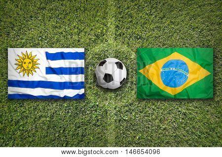 Uruguay Vs. Brazil Flags On Soccer Field, 3D Illustration