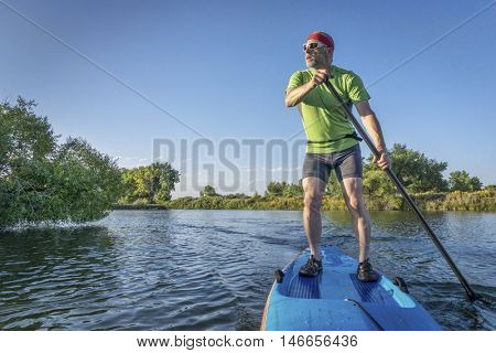 muscular, senior male paddling  a stand up paddleboard on a lake in Colorado