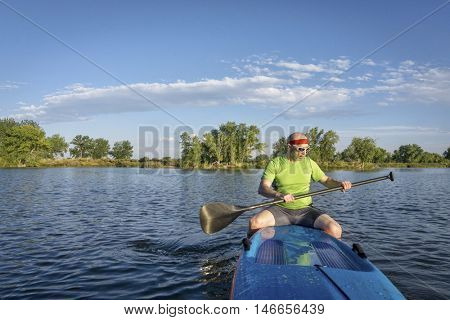 muscular, senior male paddler sitting on a stand up paddleboard on a lake in Colorado