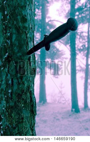 Combat knife in tree bark modified background colours .