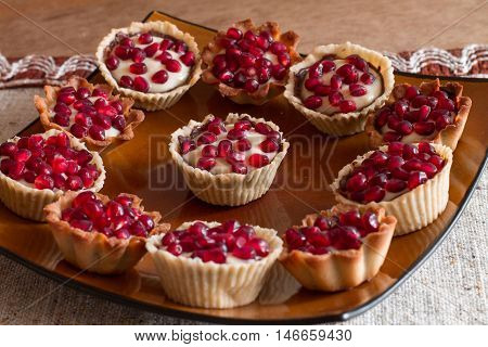 Tartletes with custard and pomegranate in big brown plate on linen tablecloth.