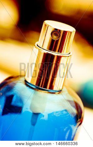Gold atomizer atop translucent blue perfume bottle