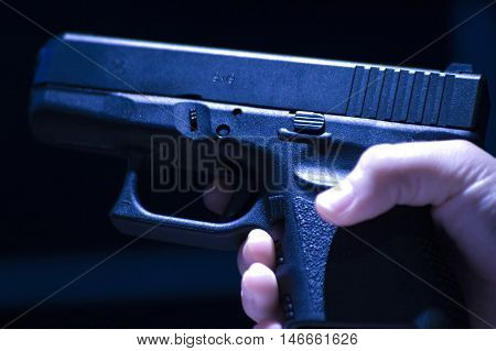 Hand holding small gun over black background.