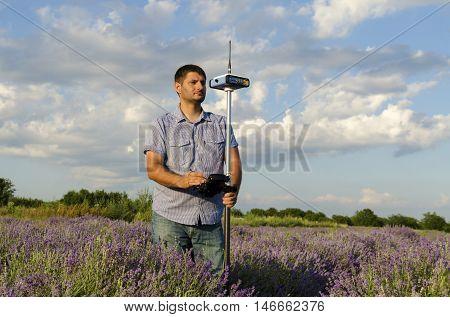 Horisontal shot of land surveyor in a lavender field