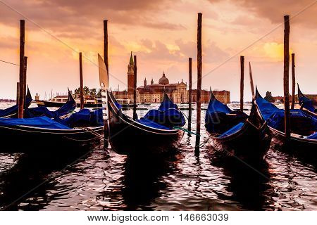 Saint Giorgio Maggiore Church in sunset, view from San Marco embankment. The church with a tower on the island and gondola in the foreground . Venice, Italy. Beautiful sunset sky in the background.