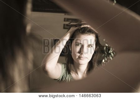 A woman looking in a mirror fixing her hair. Morning routine getting ready for the day.